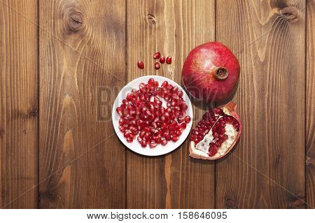 Still life with pomegranate fruit on a wooden background. Top view