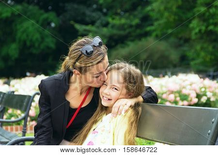 Cute kid girl hugging her mother on a summer meadow on beautiful summer sunset. Happy family together. Mum and child. Motherhood and childhood. Family playing in the garden. Outdoors.