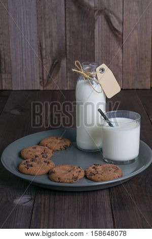 bottle of milk with carton label tag with one transparent glass, black straw and few brown cookies in gray plate on dark wooden background