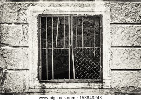 Old wall with barred window. House for demolition. Architectural element. Black and white photo.