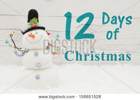 Days of Christmas message Some snow and a snowman on weathered wood with text 12 Days of Christmas