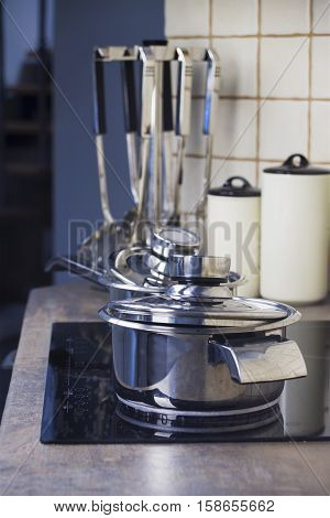 Stainless steel cooking pot on a stove and kitchenware in a background