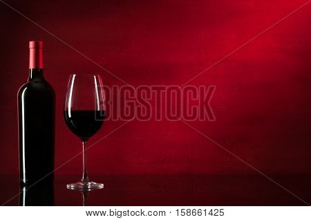 Bottle of red wine and glass. Closeup.