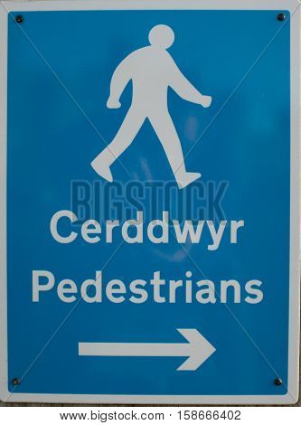 An English/Welsh language bilingual pedestrian sign with a figure words and an arrow in white on a blue background.
