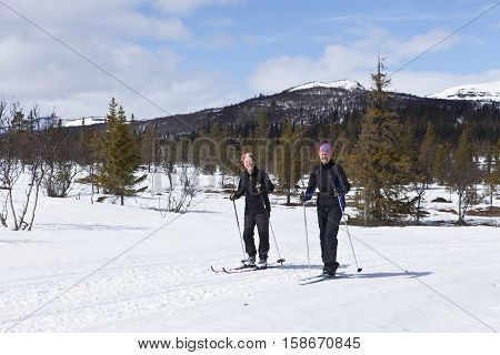 SCANDES, SWEDEN ON APRIL 27. View of two unidentified women cross-country skiing along a trail on April 27, 2013 in the Scandes, Sweden. Track and forest.
