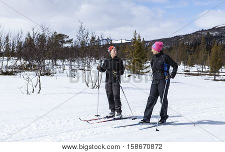 SCANDES, SWEDEN ON APRIL 27. View of two unidentified women cross-country skiing along a trail on April 27, 2013 in the Scandes, Sweden. Track and forest. Editorial use.
