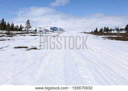Snowmobile trail, tracks and signs in the snow, springtime. Tussock and wetland both sides. Mountains in the background.