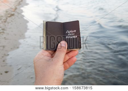Explore Dream Discover. Hand holding a book with the inscription, waves on the background.