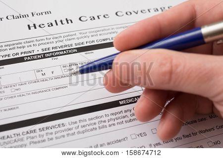 Health insurance claim form and writing hand