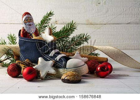 Childrens shoes filled with sweets cookies and christmas decoration for Nicholas day on the 6th December in Germany in front of white rustic wood with copy space selective focus narrow depth of field