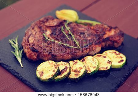 Rib-eye steak with vegetables on a slate plate, toned image