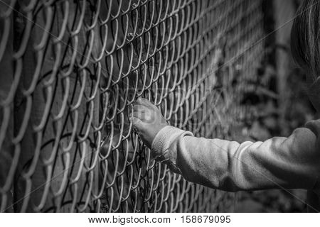 Little girl hand holding fence - Black and white image of a little girl hand grabbing a metal fence depicting drama