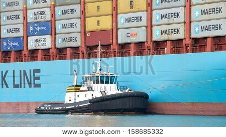 Oakland CA - October 11 2016: Tugboat DELTA CATHRYN assisting GUNVOR MAERSK to maneuver into the Port of Oakland. Tugboats are vital for safe efficient entry and exit for the large ships.