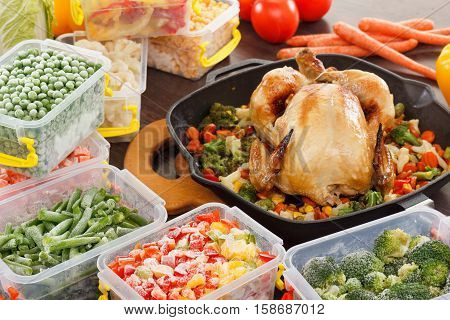 cooking frozen vegetables in plastic containers roasted chicken in pan. Healthy freezer food and meals.