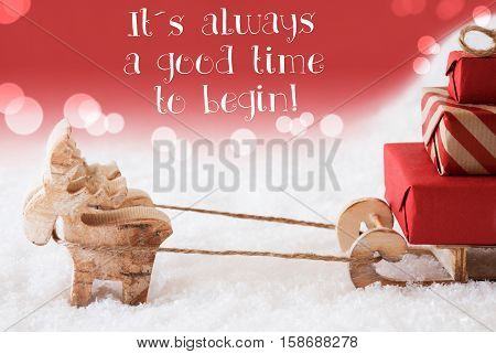 Moose Is Drawing A Sled With Red Gifts Or Presents In Snow. Christmas Card For Seasons Greetings. Red Christmassy Background With Bokeh Effect. English Quote There Is Always A Good Time To Begin