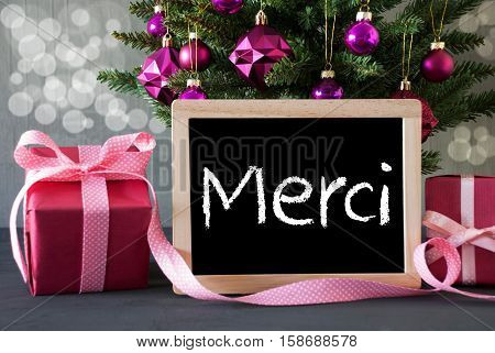 Chalkboard With French Text Merci Means Thank You. Christmas Tree With Rose Quartz Balls And Bokeh Effect. Gifts Or Presents In The Front Of Cement Background.