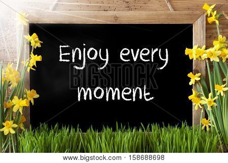 Blackboard With English Quote Enjoy Every Moment. Sunny Spring Flowers Nacissus Or Daffodil With Grass. Rustic Aged Wooden Background.
