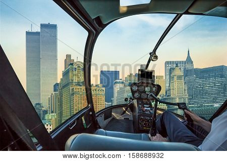 Helicopter cockpit flies in New York City with World Trade Center and Twin Towers, Manhattan, United States, with pilot arm and control board inside the cabin.
