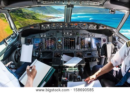 Cockpit and board of an airplane flying in Misty Cliffs, Cape Peninsula in South Africa, with pilots arms and blank white papers for copy space.