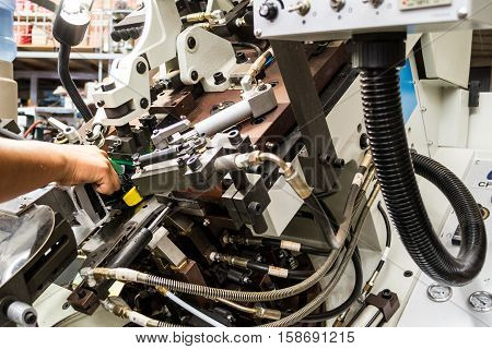 Horizontal photo in color and shallow depth of field of a shoe manufactoring machine made of metal, hydraulics
