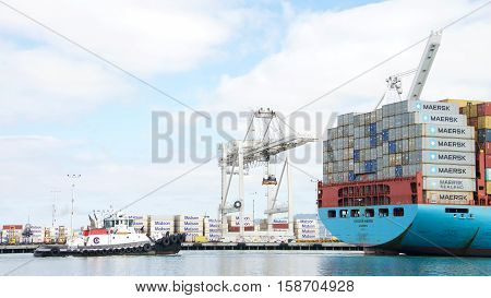 Oakland CA - October 11 2016: Tugboat VETERAN at the stern of cargo ship GUNVOR MAERSK assisting the vessel to maneuver into the Port of Oakland.