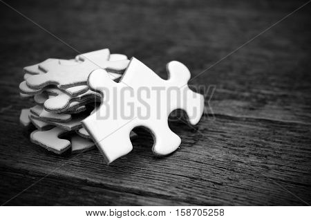 A black and white image of white jigsaw puzzle pieces stacked on an old wooden table.