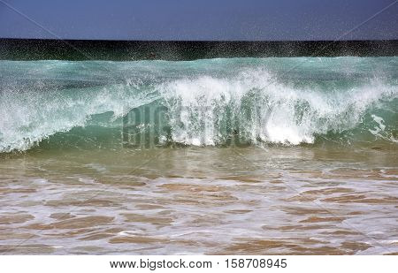 White spray splashing on the beach. Ocean tidal waves breaking on a sand beach splashing.