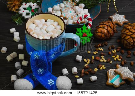 Christmas homemade gingerbread cookies hot drink chocolate marshmallow. Christmas snowflakes. Christmas drink hot cocoa chocolate in blue plate scarf. Ingredients for hot chocolate marshmallow nuts
