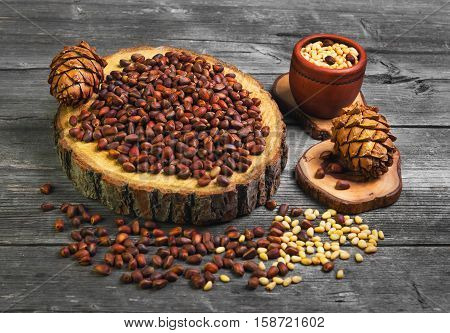 Pine nuts (cedar nuts) uncleaned on wooden frame. Peeled pine kernels on gray background rustic wooden table. Pine cones (cedar nuts) with nuts.