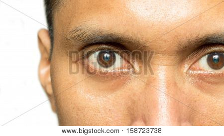 A man who looking deep with a sharp gaze makes an object reflection on his eyes.