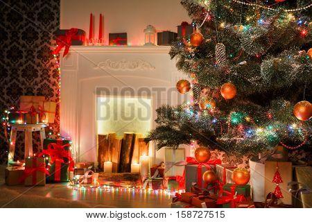 Christmas living room decorations, fireplace closeup. Beautiful xmas lights, candles, illuminated decorated christmas tree in garlands. Modern interior design, winter holidays magic night atmosphere.