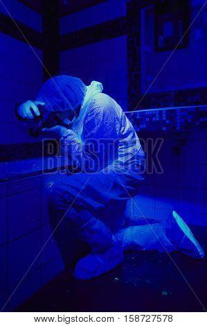 Criminologist at work on place of crime under UV light