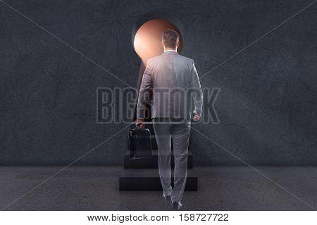 Businessman walking towards light from keyhole