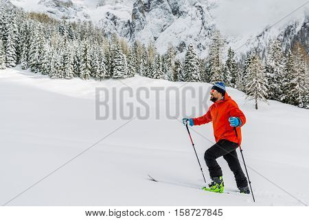 Mountaineer standing up along a snowy ridge with skis. In background snowy mountains. Adventure,  extreme sport.