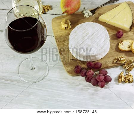 A photo of a tasting with two glasses of wine, red and white, different types of cheese, bread, nuts, pear, grapes, on a wooden board with copyspace