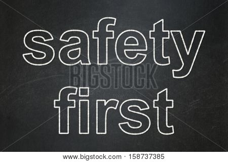 Security concept: text Safety First on Black chalkboard background