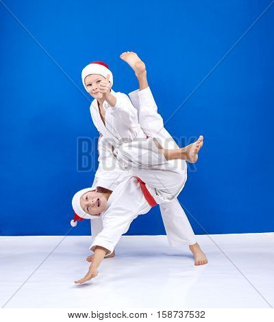 Athletes are training judo throws on the blue background