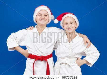 Girl and boy in Santa hat on the blue background