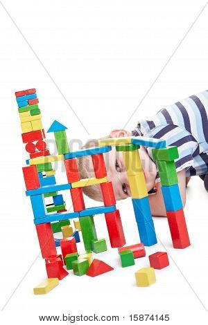 Child Looking Through Building Blocks