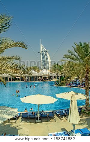 DUBAI, UAE - OCTOBER 14, 2016: The iconic Burj al Arab hotel in Dubai with hotel pool in foreground. Built on a man made island, The Burj al Arab is the only 7 star hotel in the world