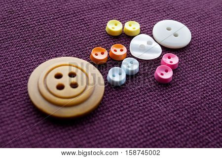 Cute sewing buttons man. Funny character with love white heart button. violet textile background. macro view