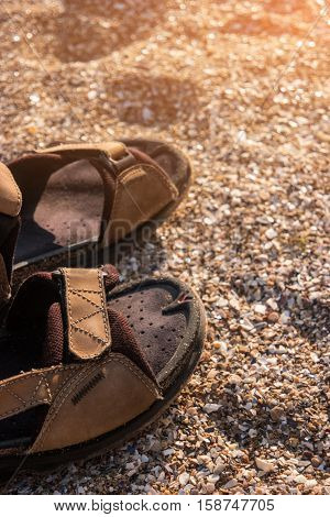 Shoes on sand background. Sandals of brown color. Spend summer vacation on island. Path of the adventurer.