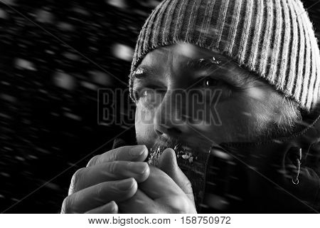 Freezing cold man standing in a snow storm biazzard trying to keep warm. Wearing a beanie hat and winter coat with frost and ice on his beard and eyebrows. Black and white.