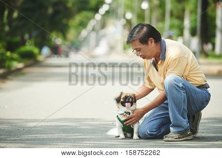Dog lover petting his cute little dog