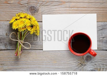 Bouquet of dandelions blank paper and coffee cup top view