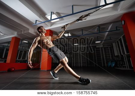 Fitness man workout on the rings. Fitness man in the gym. Fitness style. Workout on rings. Sport and fitness