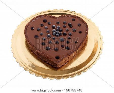 Delicious chocolate cake with blueberries in form of heart on golden cardboard stand. Isolated on a white background.