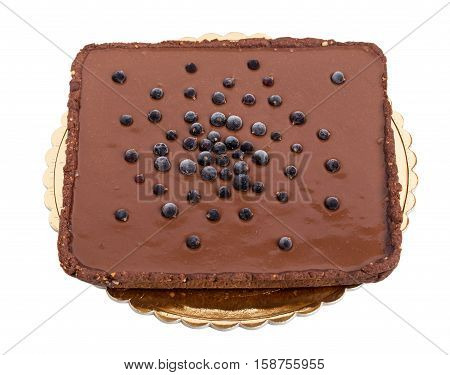 Delicious chocolate cake with blueberries on golden cardboard stand. Isolated on a white background.
