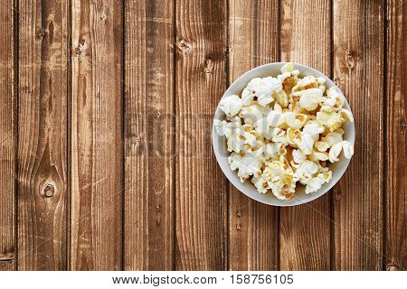 Popcorn in bowl on wooden background top view