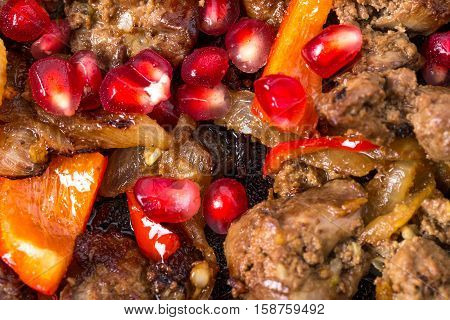 Stewed chicken livers with paprika and pomegranate seeds. Macro.